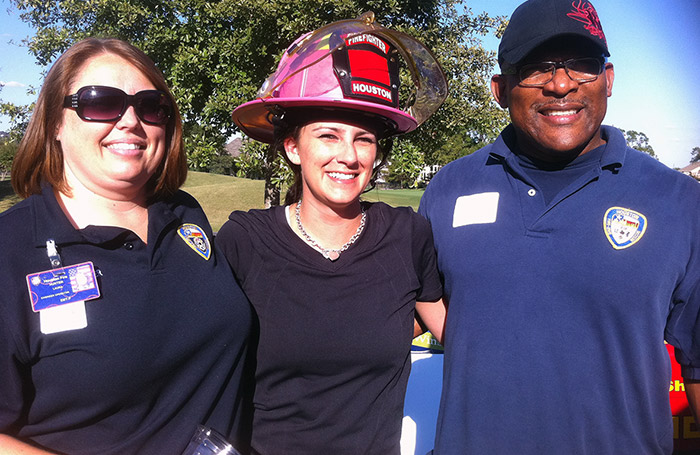 Texas Floor Covering, Inc. VP Michelle Hatton with firefighters at the Houston BOMA Golf Classic.